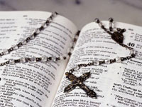 Photo of a rosary looped across an open Bible.